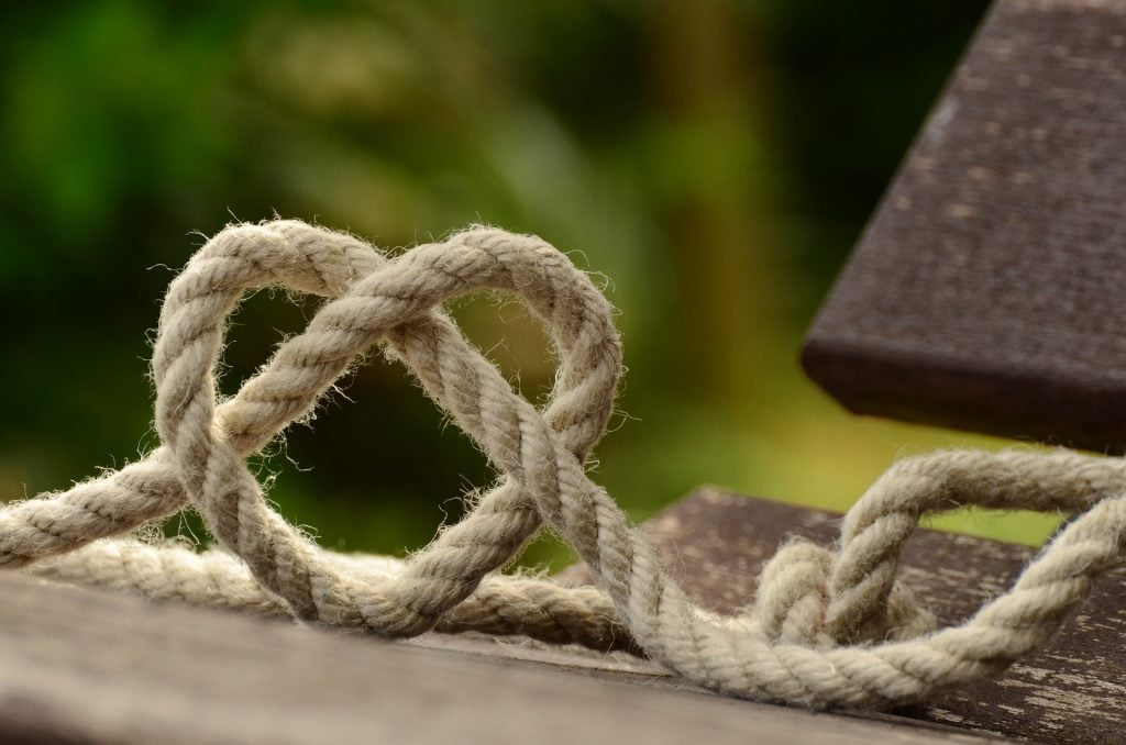 heart made out of braided rope on wooden bench