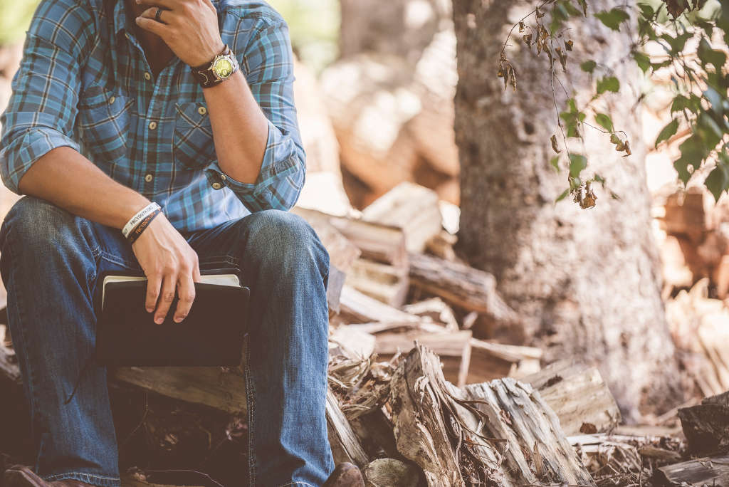 man in plaid shirt sitting with bible