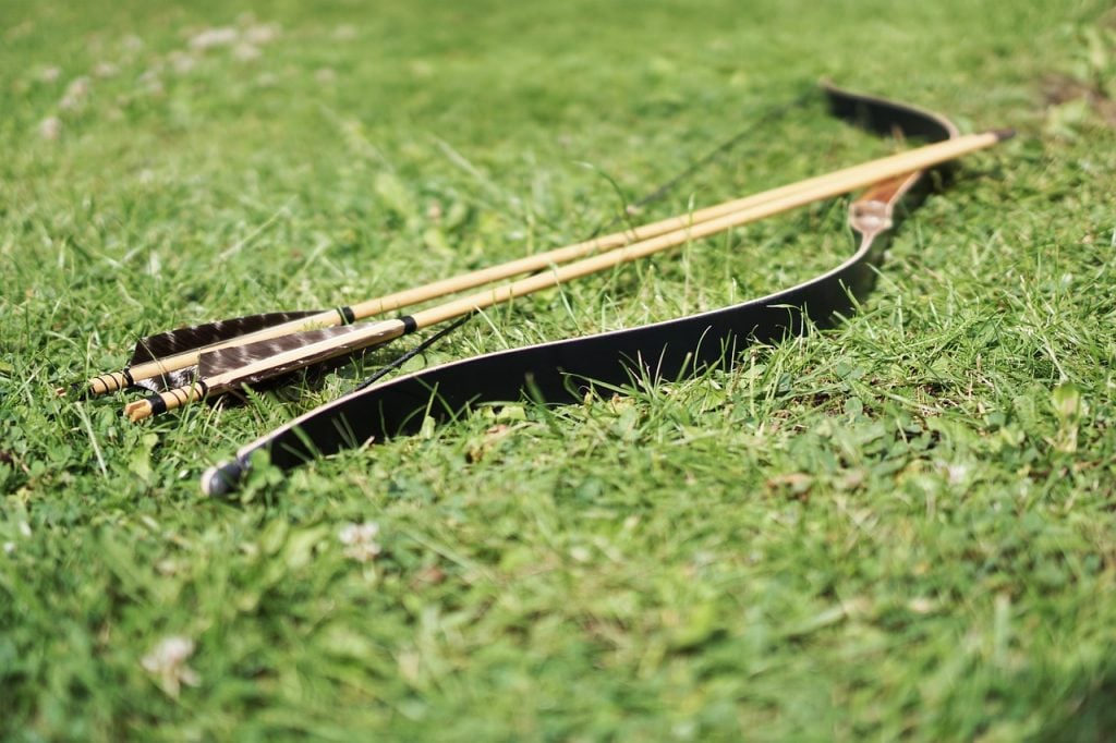 bow and arrows lying in grass bible verses are like arrows