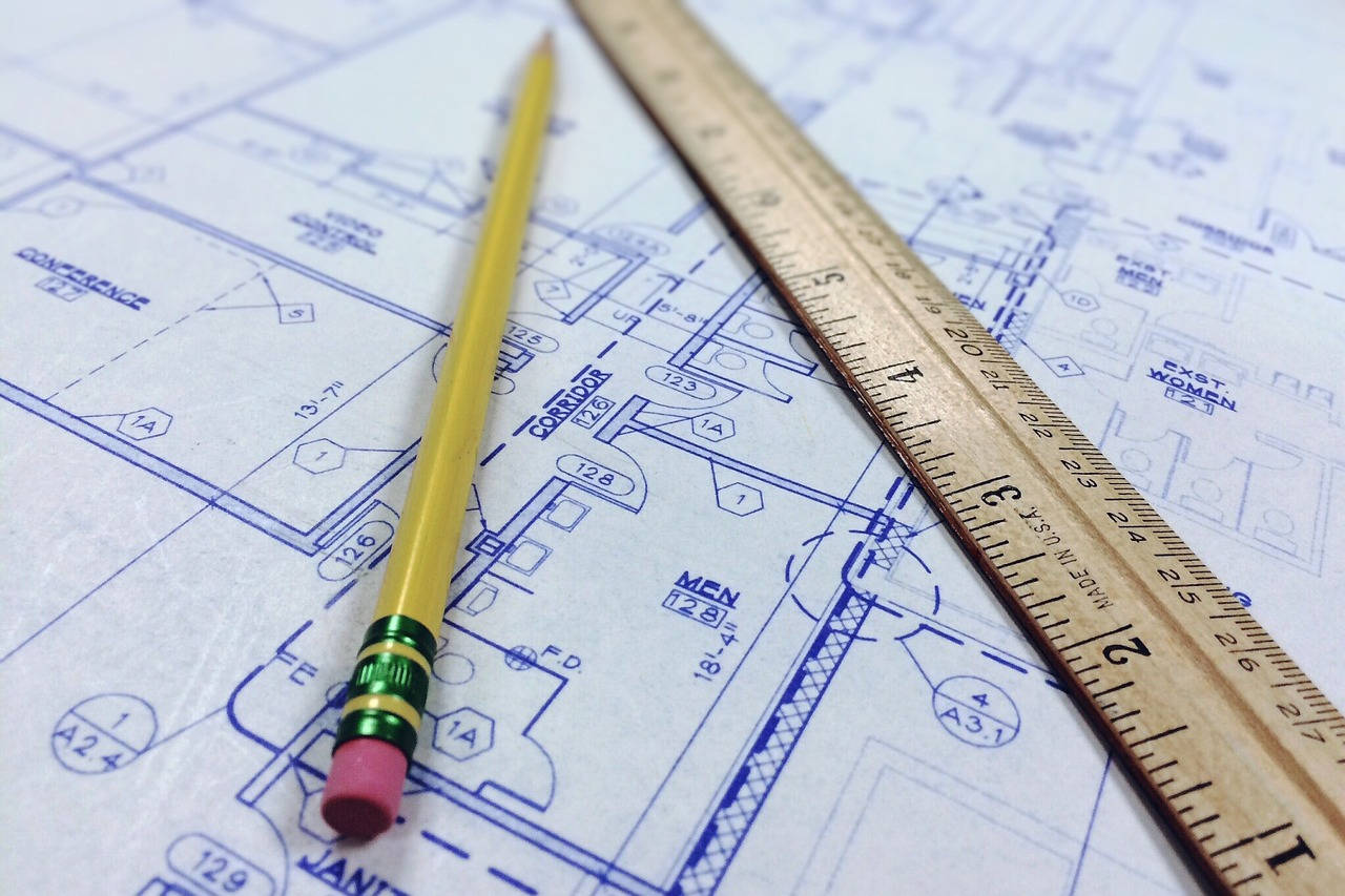 Architect's blueprint on table with wooden pencil and wooden ruler