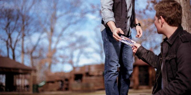 man sitting outdoors handing church invitation to man walking by
