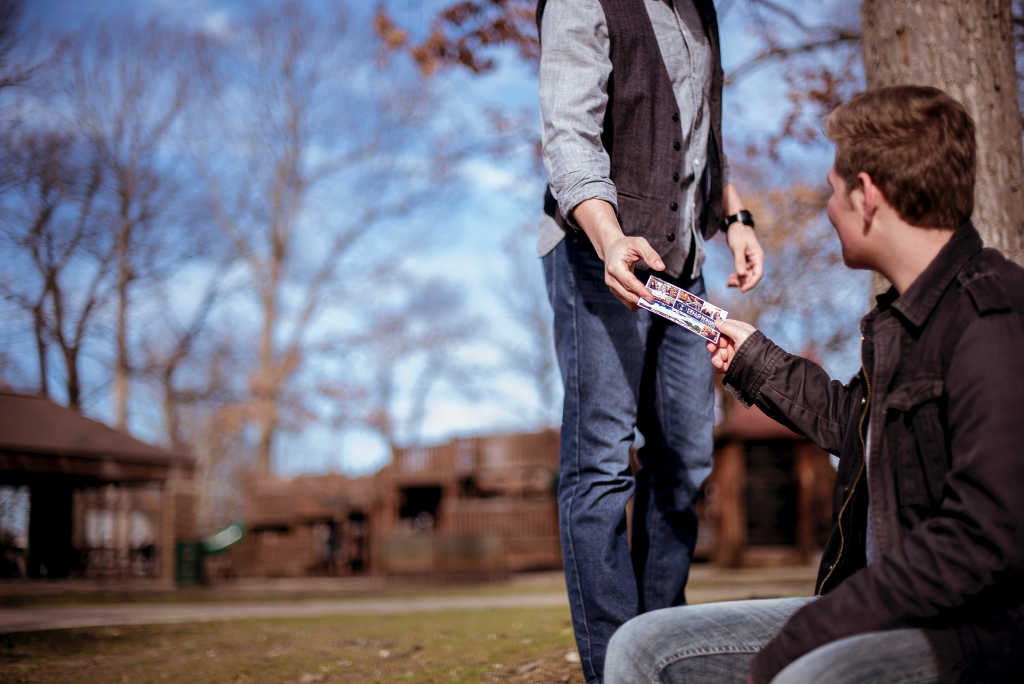 man sitting outdoors handing church invitation to man walking by