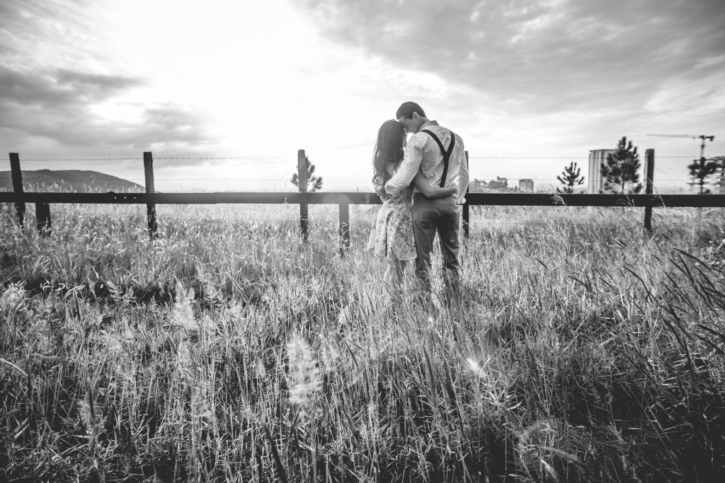 couple embracing in open field, men love your wife