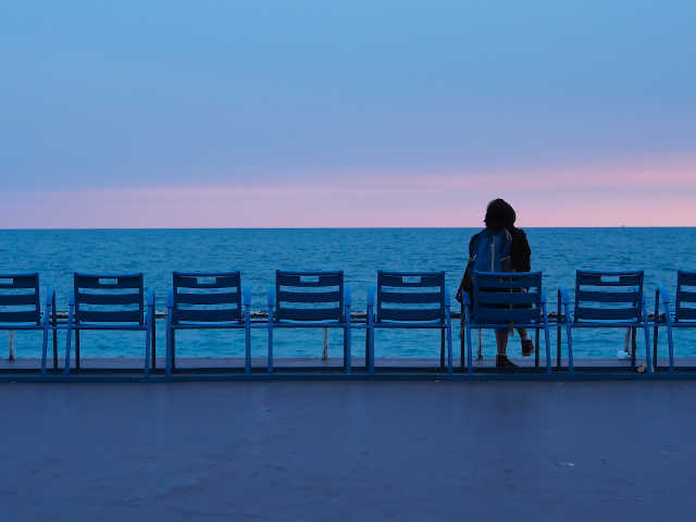 woman sitting alone looking over the sea with a dark blue sky