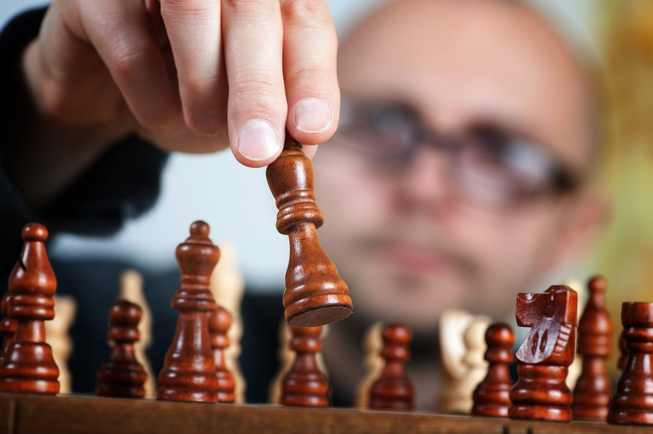 chess player moving a wooden chess piece